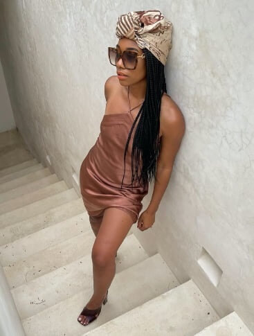 La mannequin porte une robe en satin bronze et des lunettes de soleil.