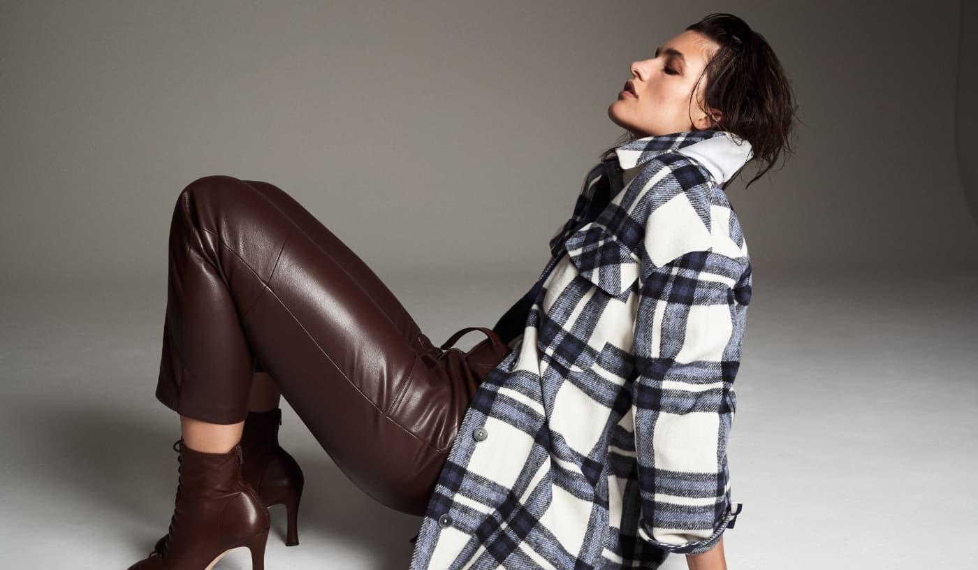 Une mannequin porte une veste-chemise avec un pantalon brun en faux cuir et les bottes assorties.