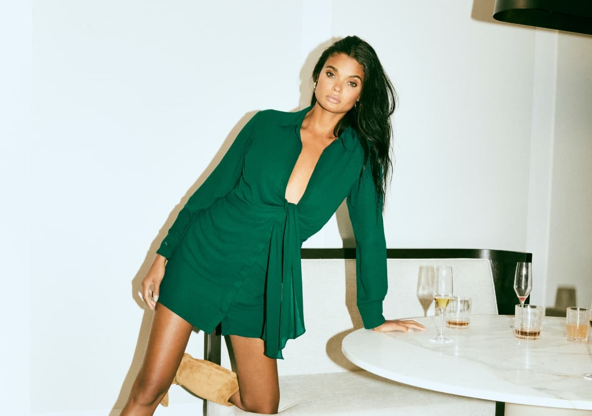 A model wears a green wrap dress while leaning on a table.