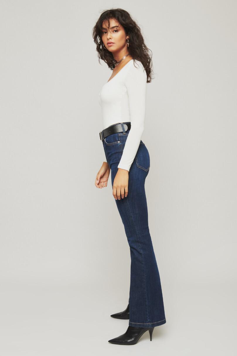 Model is wearing dark wash jeans.