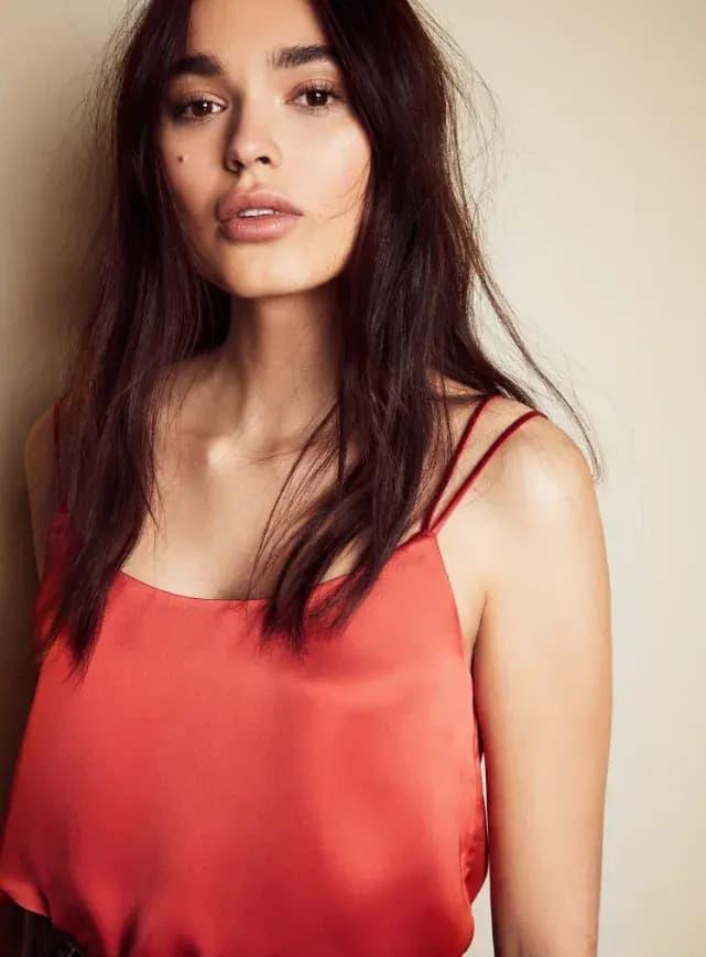 A model wears a pink satin tank top.