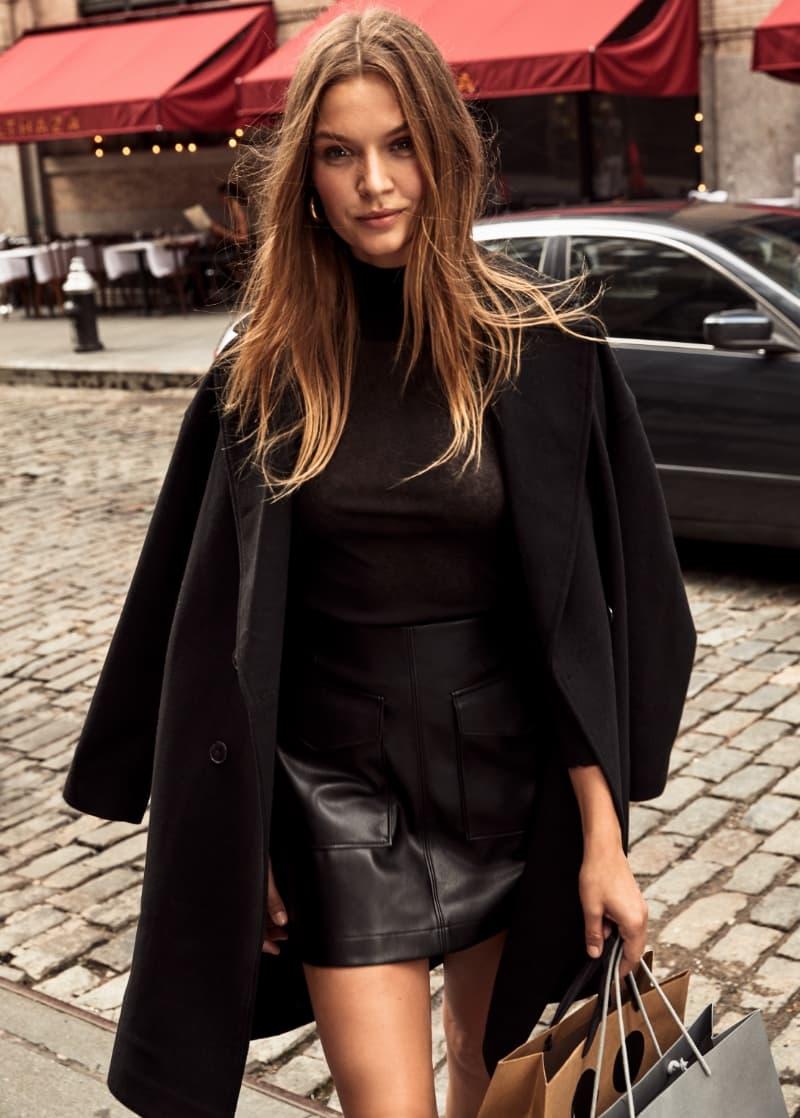 Une mannequin porte une robe enveloppante, un col roulé noir et une jupe noire en faux cuir.
