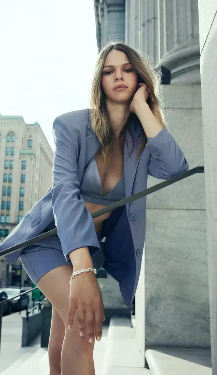 A model wears a purple bralette with a matching blazer and shorts.
