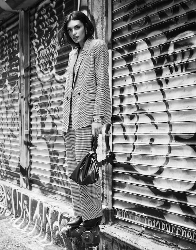 Une mannequin porte un blouson à carreaux et un pantalon assorti.