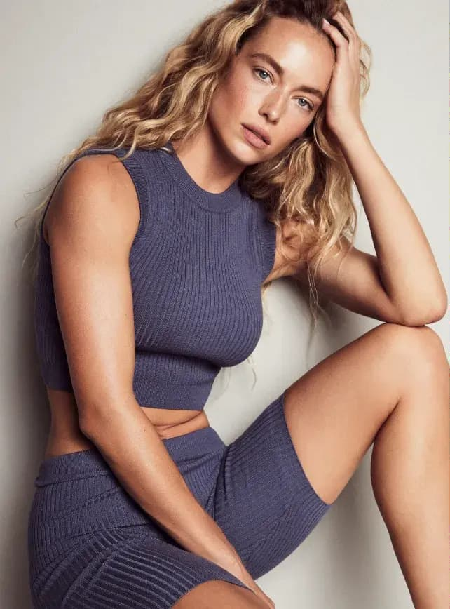 A model wears a blue knit cropped tank with matching biker shorts.