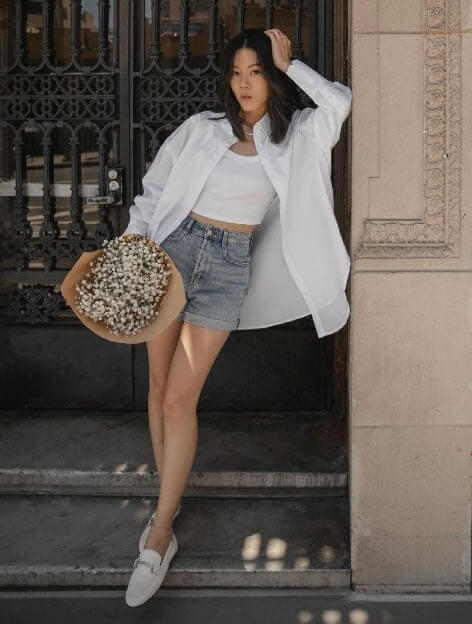 Model is wearing denim shorts and a white shirt.