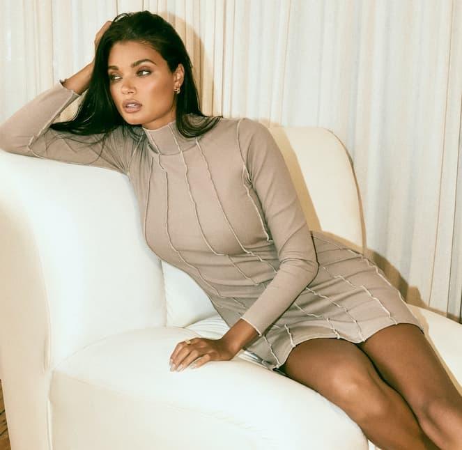 A model wears a long-sleeved beige mini-dress.