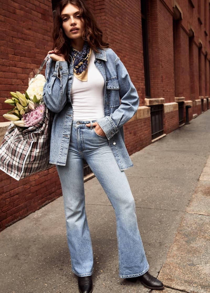 A model wears a denim shirt jacket, jeans and a white t-shirt.