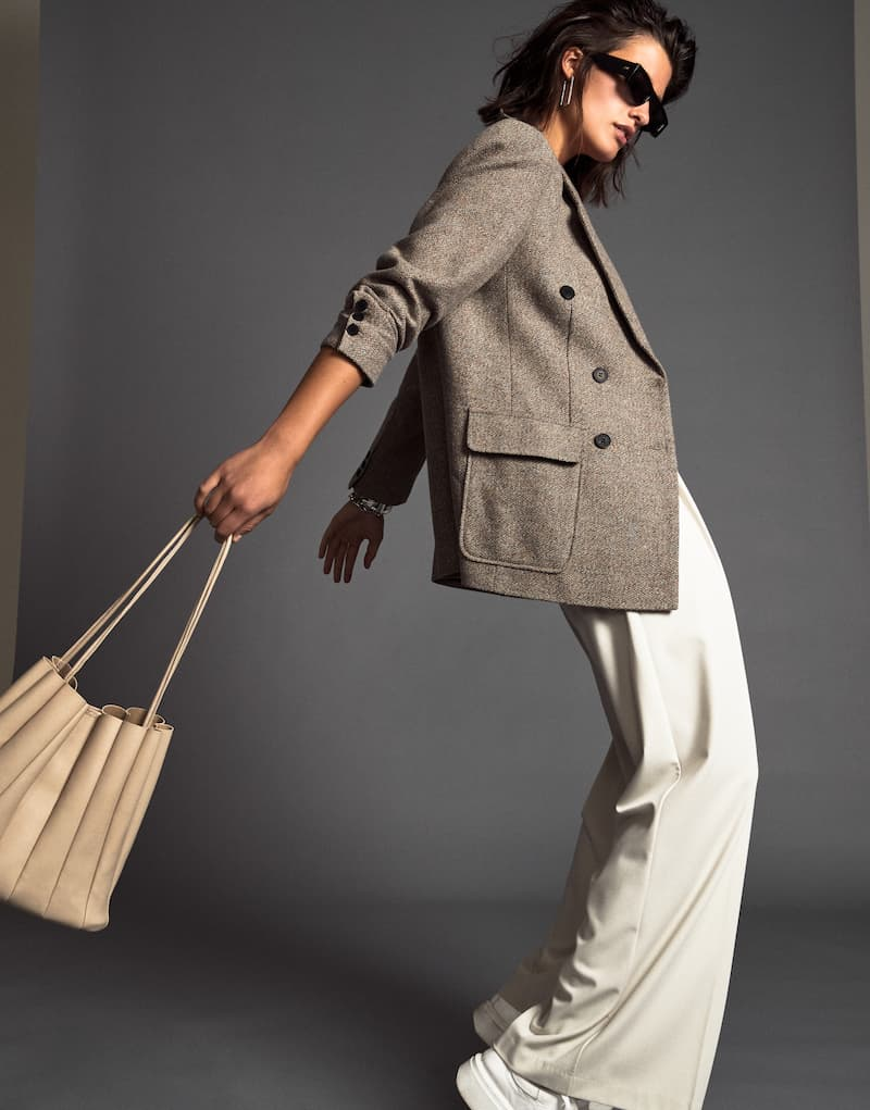 A model wears a brown jacket and cream wide-leg pants.