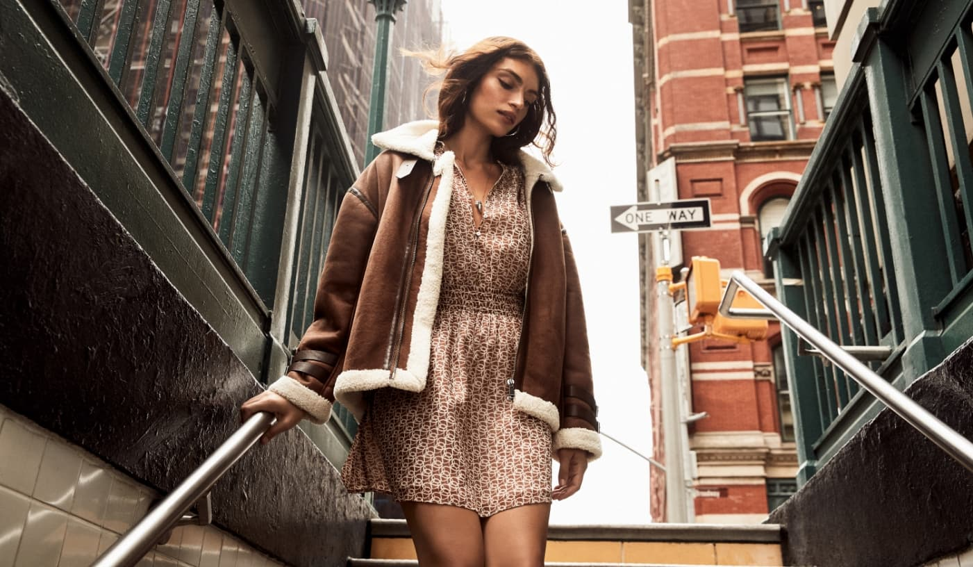 A model wears a printed fit-and-flare mini dress with a suede shearling jacket.
