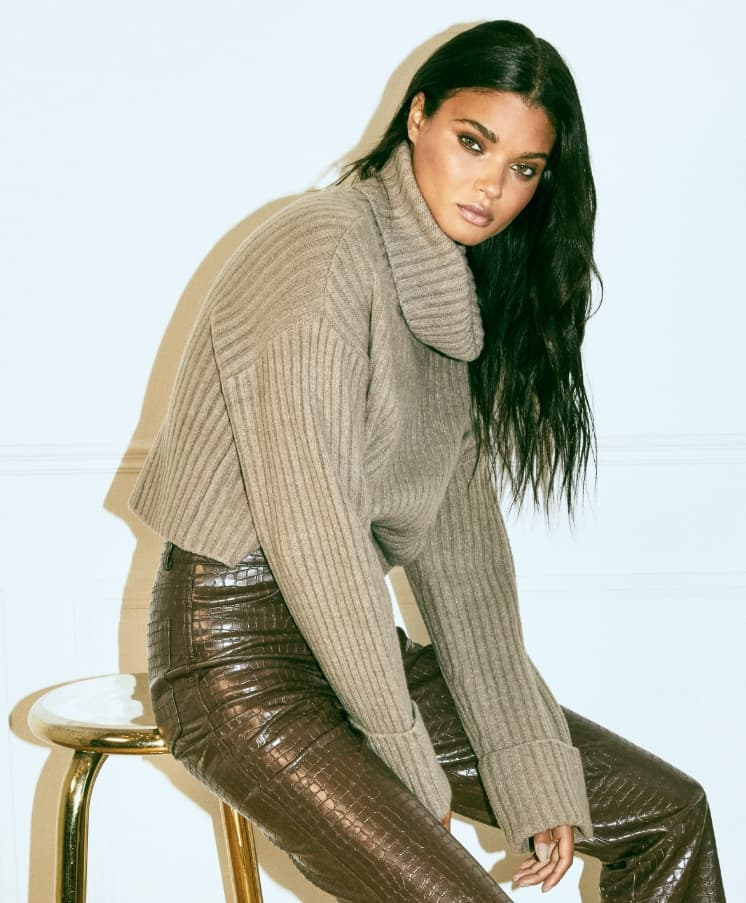 A model wears a brown rib-knit turtleneck and brown croco faux leather pants.