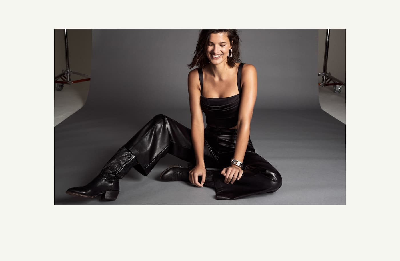 A model wears a square-necked black satin tank, black faux leather pants and black boots.