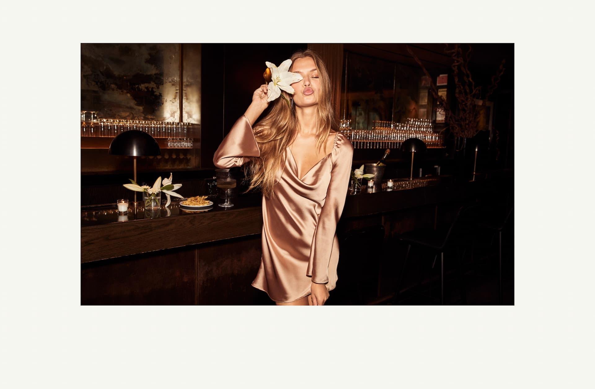 A model wears a long-sleeved pink satin minidress.