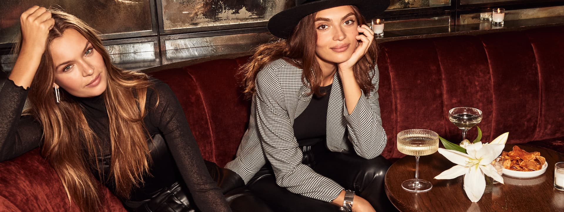 A model wears a sheer black long-sleeved top and faux leather pants. Another model wears a checked blazer and black hat.