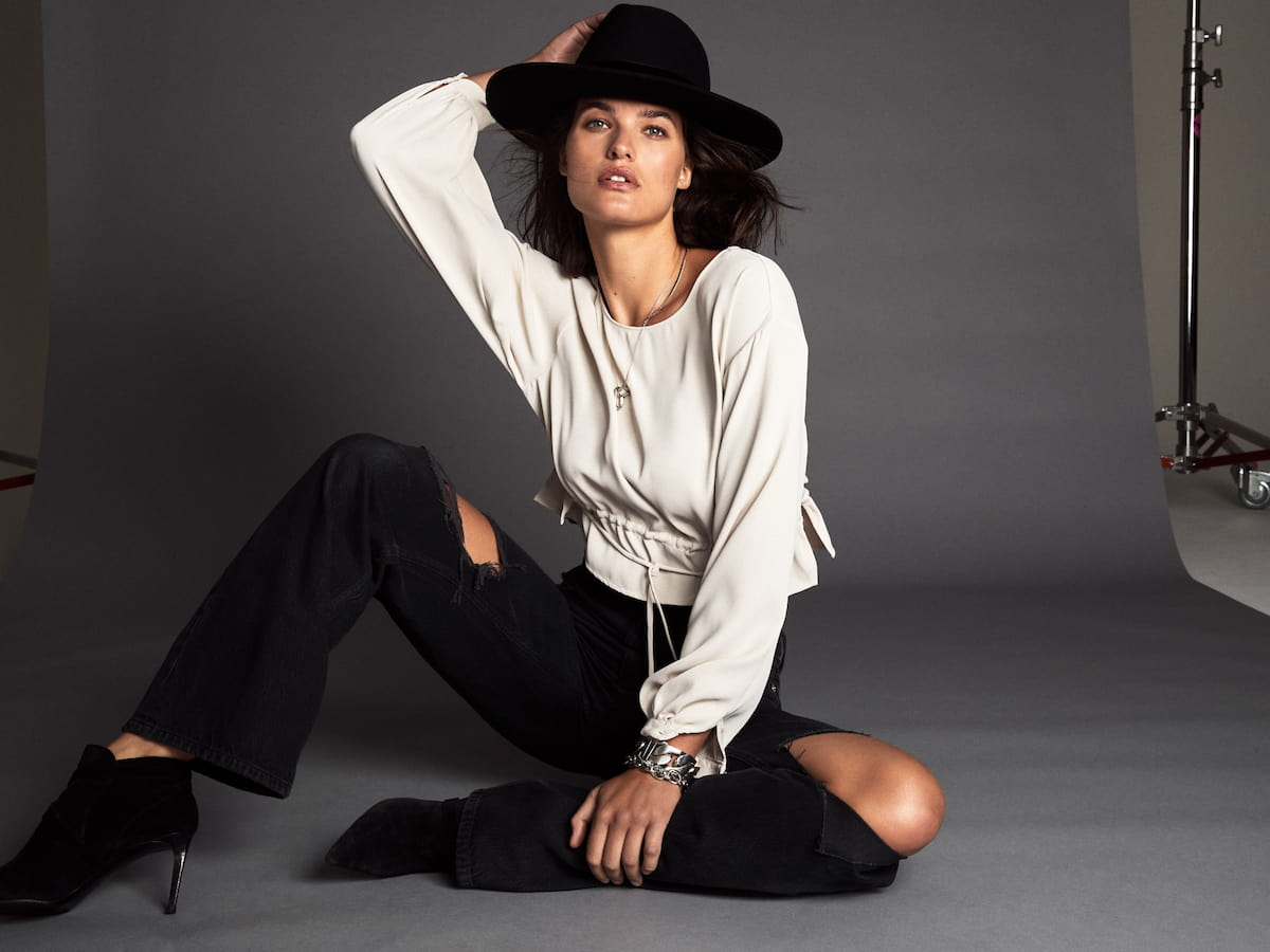 A model wears a long-sleeved white blouse with black jeans.
