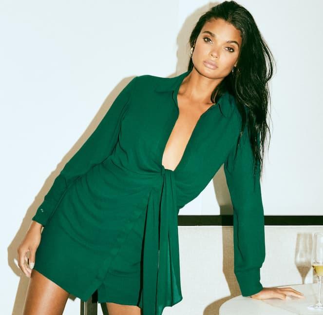 A model wears a green tie-front shirtdress.