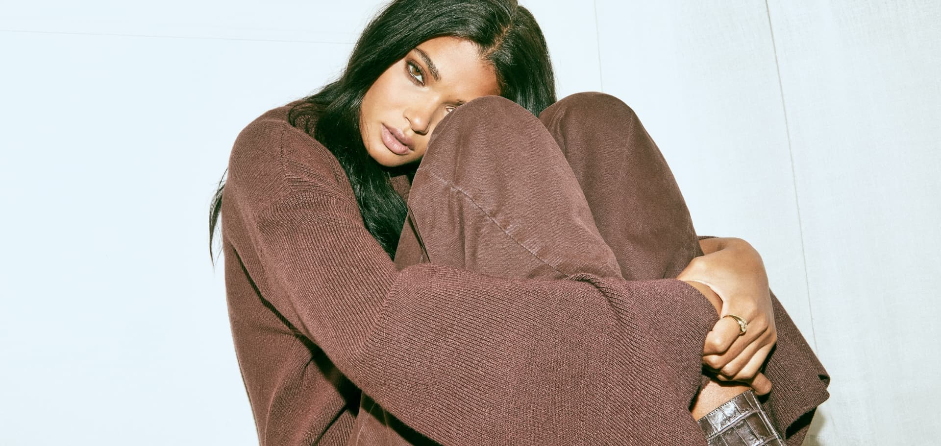 A model wears a brown sweater and matching pants.