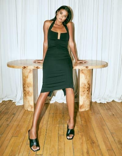 A model wears a black bodycon midi dress.
