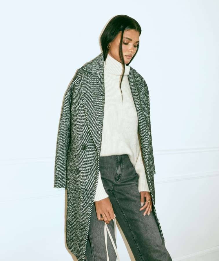 A model wears a grey cocoon coat, white turtleneck sweater and black jeans.