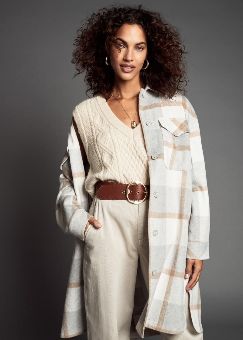 A model wears a plaid shirt jacket with a cable knit sweater vest and beige pants.