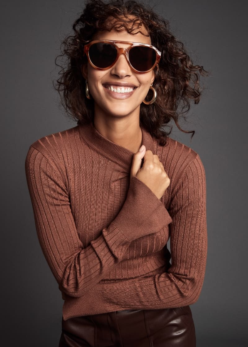 A model wears a brown ribbed mock neck sweater.
